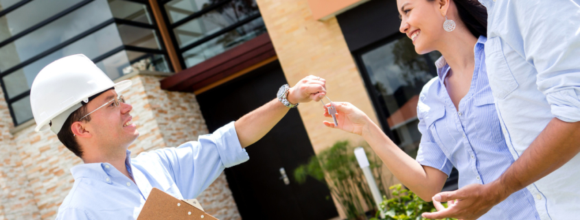 architect handling keys to a couple